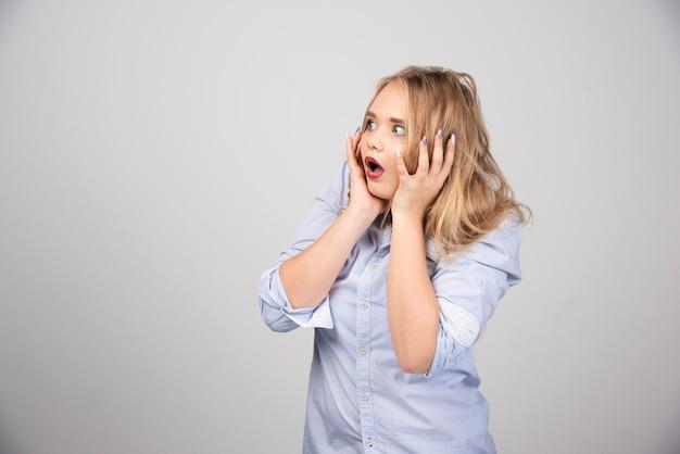 Молодая испуганная блондинка с открытым ртом, взявшись за голову.