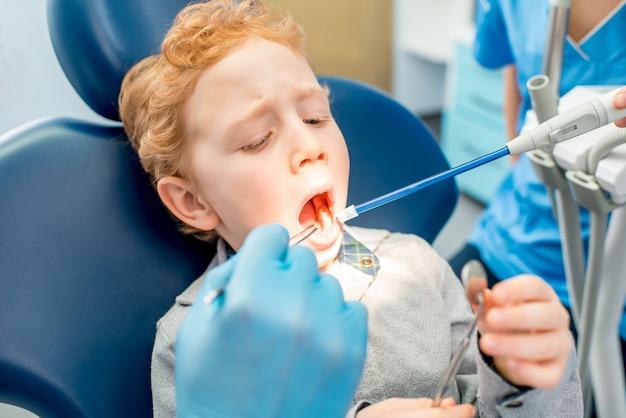 歯科医院での歯科治療中の怖がっている少年