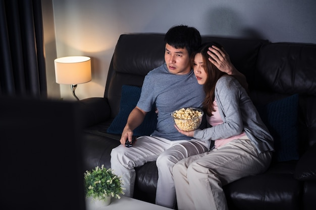 Young scared couple is watching horror movie tv on sofa at night