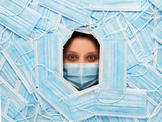 Молодая испуганная девушка в хирургической маске смотрит прямо на фоне многих медицинских масок. пандемия, закрытые границы и концепция изоляции.
