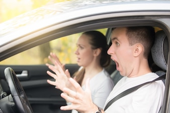 Young scared man driver and a woman passenger