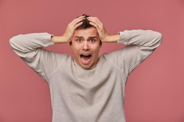 Молодой испуганный человек в пустом длинном рукаве слышит очень плохие новости, держит голову и смотрит в камеру с шокированным выражением лица, стоит на розовом фоне и кричит, выглядит испуганным.