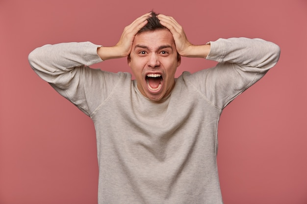 Молодой испуганный человек в пустом длинном рукаве, держит голову и смотрит в камеру с шокированным выражением лица, слышит очень плохие новости, стоит на розовом фоне и кричит, выглядит испуганным.