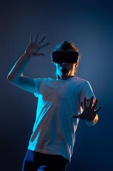 Молодой человек испугался, используя очки виртуальной реальности на синем фоне. неоновый свет.