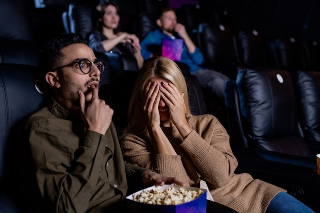 Young scared woman covering face while watching horror movie with her boyfriend eating popcorn in cinema