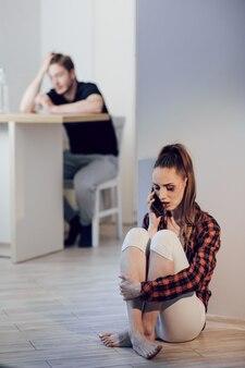 彼女の顔にあざを持つ若い怖い女性は彼女の夫から隠れるし、警察を呼び出す