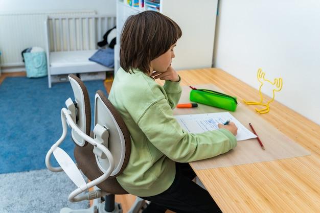 自宅のテーブルに座って宿題をしている少年。タスクについて考える集中した子供。 homeschooliong教育。