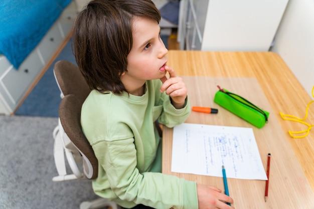 自宅のテーブルに座って宿題をしている少年。興味を持って仕事を考えている集中した子供。 homeschooliong教育。