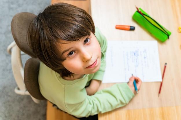 自宅のテーブルに座って宿題をしている少年。集中して子供が楽しく書く練習をします。 homeschooliongコンセプト。