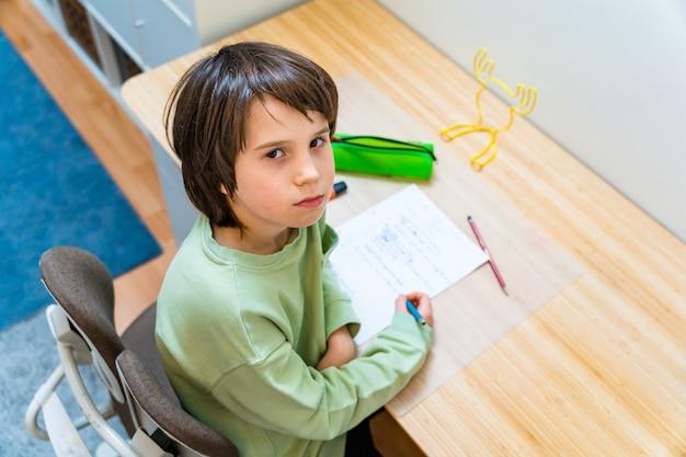 집에서 테이블에 앉아 그의 숙제를 하 고 젊은 학교 소년. 피곤하고 화가 난 아이 쓰기 연습. homeschooliong 교육.