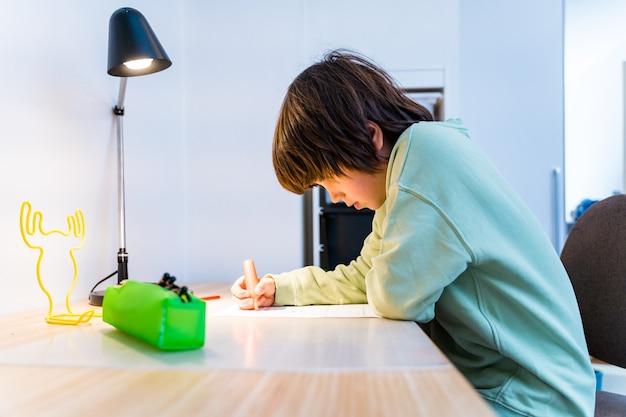自宅のテーブルに座って宿題をしている少年。