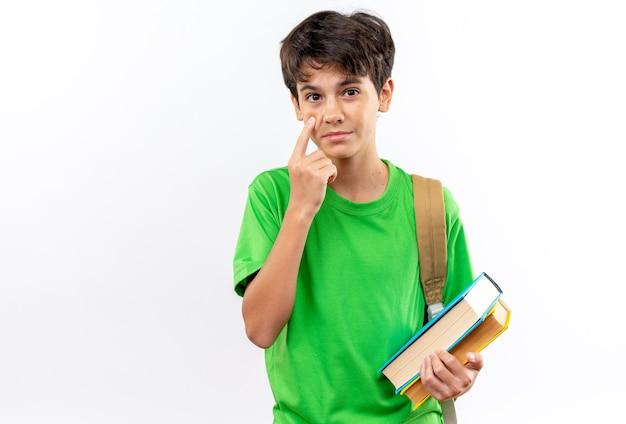 白い壁に隔離されたまぶたを引き下げる本を保持しているバックパックを身に着けている若い男子生徒