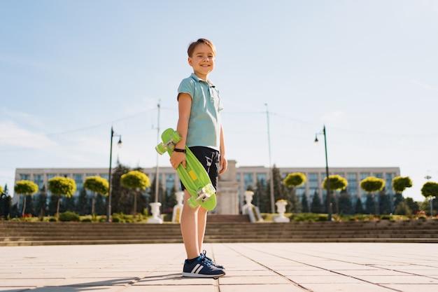 ペニーボードを手に立っている明るい服を着た若い学校のクールな男の子