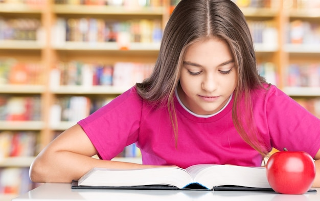 Young school girl reading a book at the library
