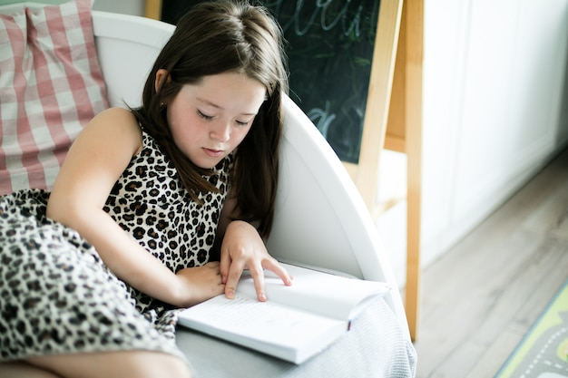 Young school girl reading a book in the room at home.