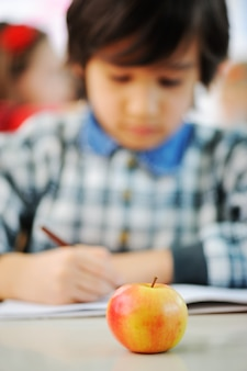 Young schoolboy drawing an apple