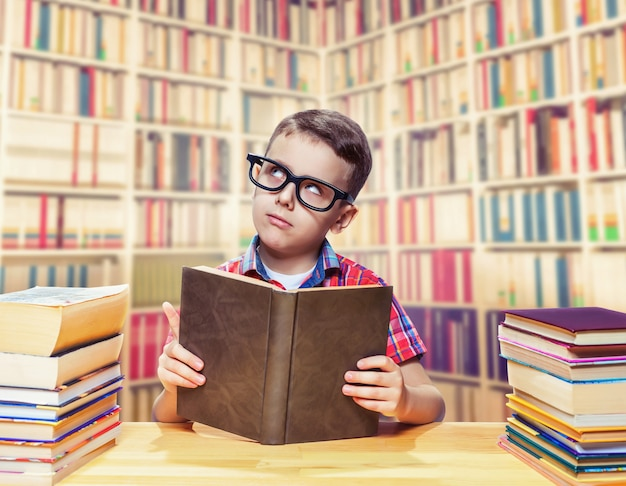 Молодой школьник в очках читает книгу в школьной библиотеке. концепция образования. получение знаний из учебника