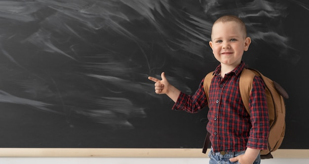 A young schoolboy near the blackboard shows his index finger to the left. a fashionable guy is wearing a plaid shirt and light jeans. on the back of the child is a brown backpack.