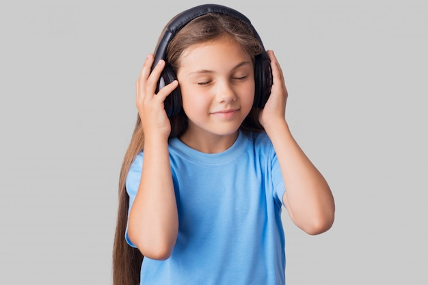 Young schoolgirl in blue t-shirt using wireless headphones for listening to music