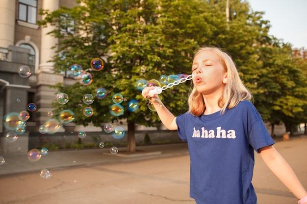도시에서 야외에서 비누 방울을 부는 것을 즐기는 어린 여학생