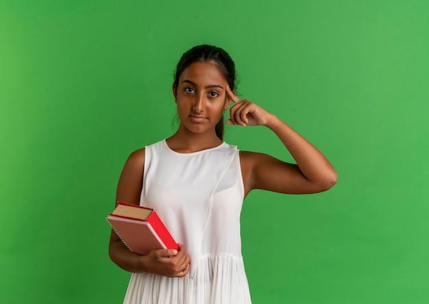 노트북으로 책을 들고 머리에 손가락을 넣어 젊은 여학생