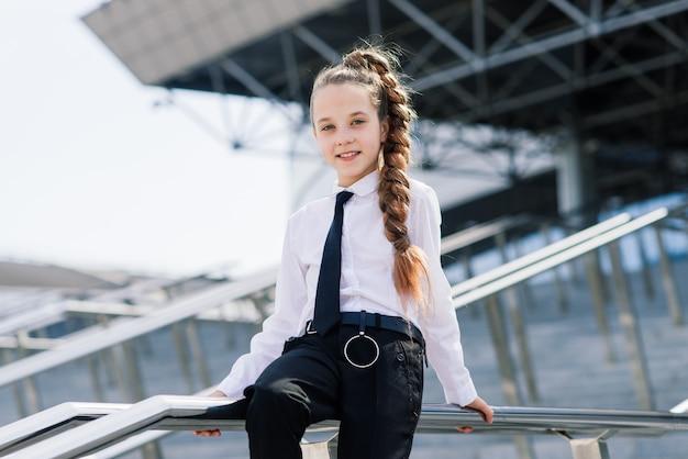 Молодая школьница в белой классической блузке позирует