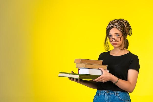 Молодая школьница в очках держит книги и делает смущенное лицо.