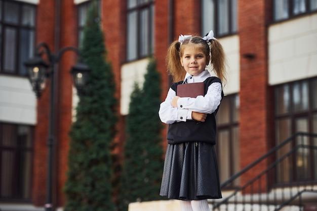 Молодая школьница в формальной одежде и блокноте в руках стоит возле здания на открытом воздухе.