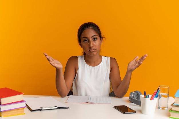 학교 도구와 책상에 앉아 젊은 여학생 손을 확산
