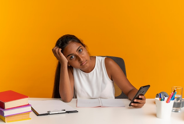 Giovane studentessa seduto alla scrivania con strumenti di scuola mettendo la testa a portata di mano e tenendo il telefono