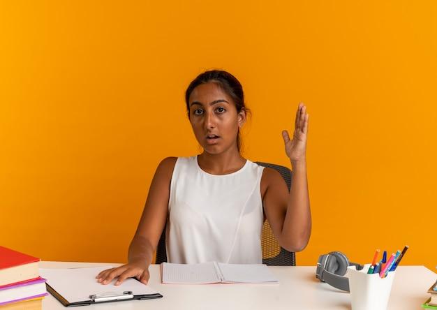 Giovane studentessa seduto alla scrivania con strumenti di scuola alzando la mano