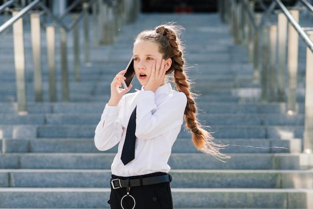 Молодая школьница разговаривает по телефону