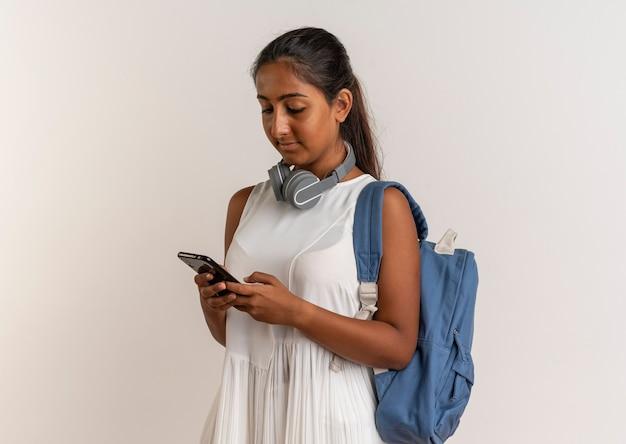 Молодая школьница в сумке и наушниках набирает номер на телефоне на белом