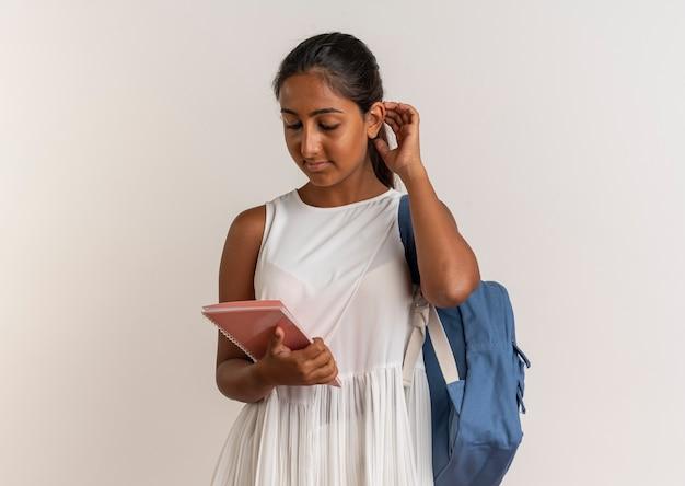 Giovane scolara che indossa la borsa posteriore che tiene e che esamina taccuino che mette la mano sulla testa su bianco
