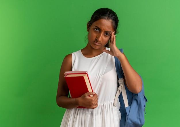 노트북과 책을 들고 이마에 손을 넣어 배낭을 착용하는 젊은 여학생