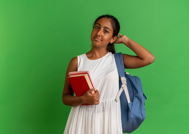 노트북과 책을 들고 머리에 손을 넣어 배낭을 착용하는 젊은 여학생