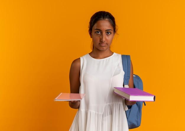 Молодая школьница в рюкзаке держит книгу с блокнотом
