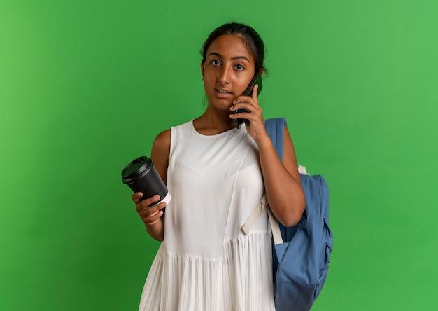 커피 한잔 들고 배낭을 착용하는 젊은 여학생과 전화로 말한다