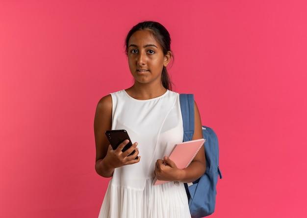 노트북으로 전화를 들고 배낭을 착용하는 젊은여 학생