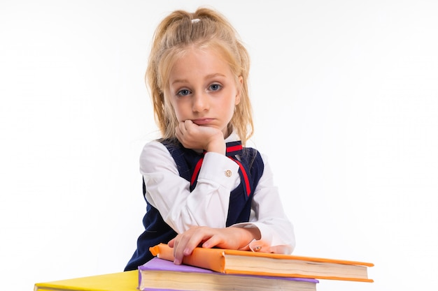 Young schoolgirl with blonde hair holds a lot of books isolated on white
