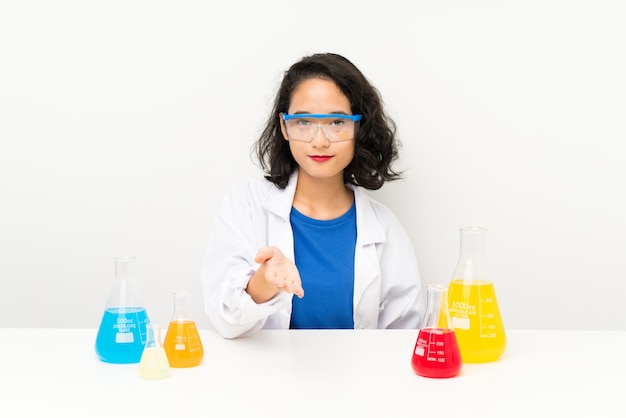 Young scientific asian girl handshaking after good deal