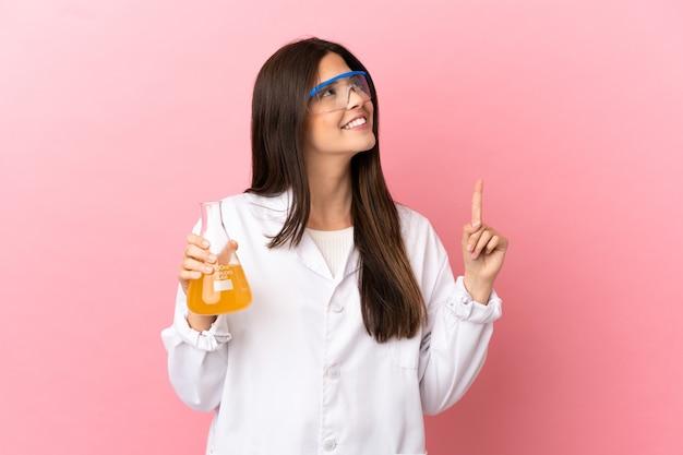 素晴らしいアイデアを指している孤立したピンクの背景上の若い科学的な女の子