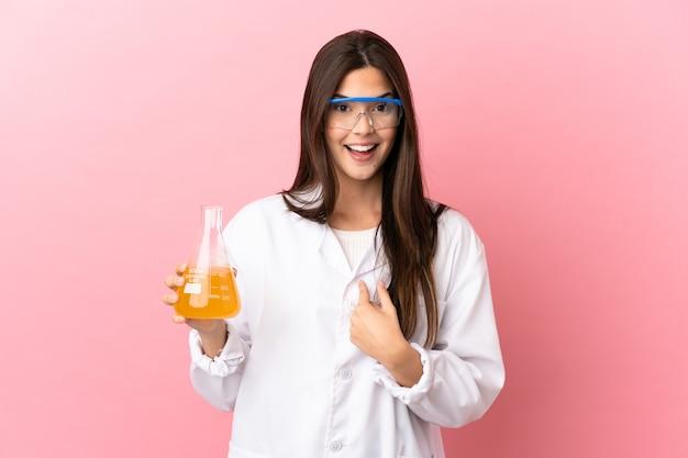 놀라운 표정으로 고립 된 분홍색 배경 위에 젊은 과학 소녀