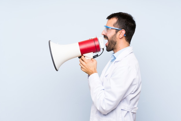 Young scientific holding laboratory flask over isolated background shouting through a megaphone