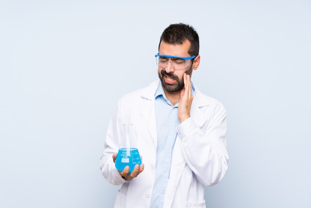 Young scientific holding laboratory flask over isolated background with toothache