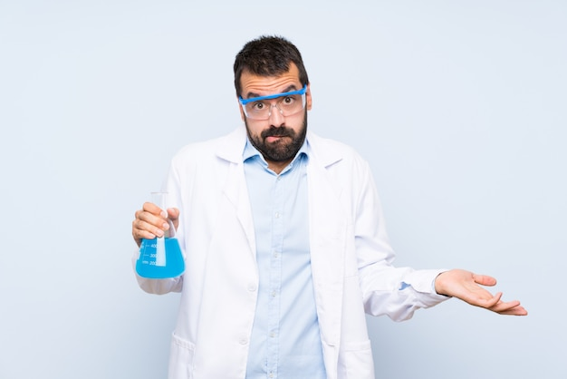 Young scientific holding laboratory flask over isolated wall having doubts while raising hands