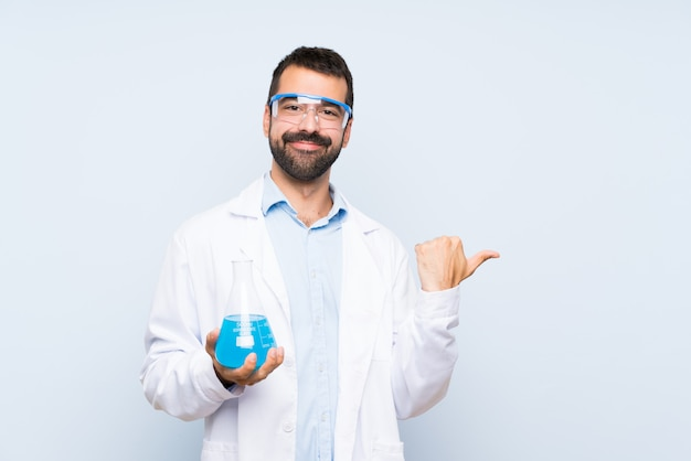 Young scientific holding laboratory flask over isolated wall pointing to the side to present a product