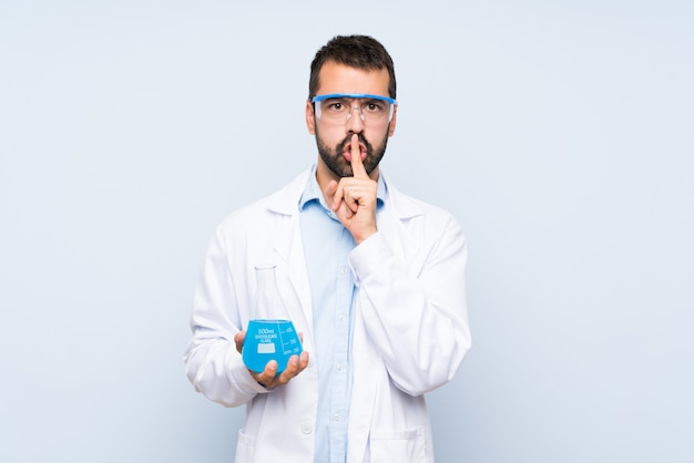 Young scientific holding laboratory flask over isolated wall showing a sign of silence gesture putting finger in mouth