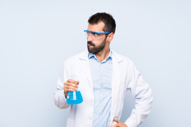 Young scientific holding laboratory flask over isolated  with confuse face expression