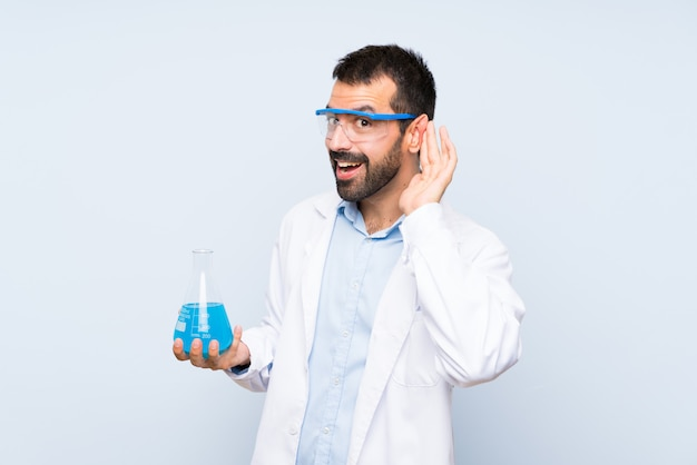 Young scientific holding laboratory flask listening to something by putting hand on the ear